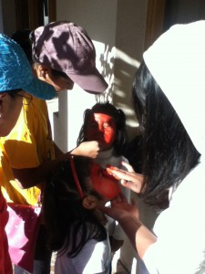Our Little Pedacitos and Corazón chicas dressed as stop-lights. Victoria and Zamora are getting their faces painted.