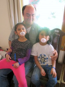 Tío Jose with Nohemi and Karina happy as can be enjoying the bubble gum found in their stockings.